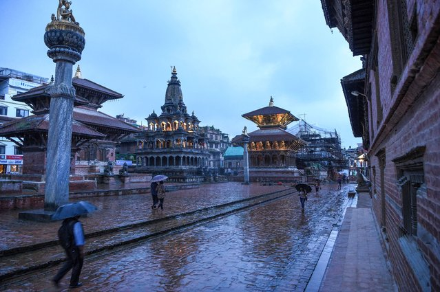 Residents carrying umbrellas walk on an almost deserted Durbar Square under the rain after restrictions were imposed by district officials for a week to contain the spread of the COVID-19 coronavirus, in Patan (Lalitpur) on the outskirts of Kathmandu on August 26, 2020. (Photo by Prakash Mathema/AFP Photo)