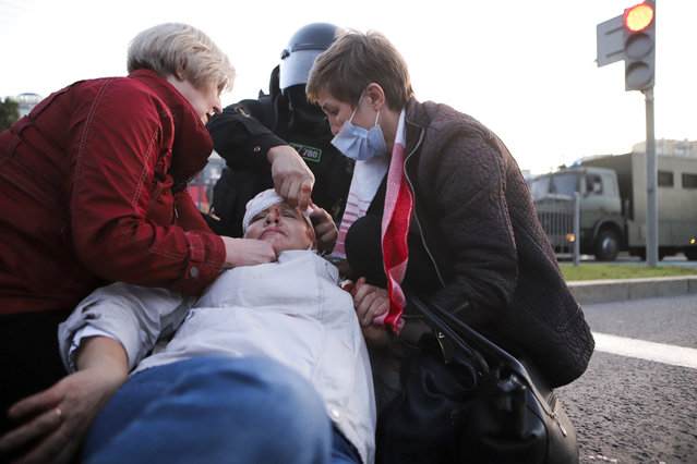 Two women provide a health care to a wounded protester during an opposition rally to protest the presidential inauguration in Minsk, Belarus, Wednesday, September 23, 2020. Belarus President Alexander Lukashenko has been sworn in to his sixth term in office at an inaugural ceremony that was not announced in advance amid weeks of huge protests saying the authoritarian leader's reelection was rigged. Hundreds took to the streets in several cities in the evening to protest the inauguration. (Photo by AP Photo/Stringer)