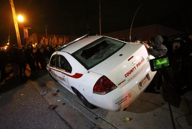 Protesters rock a vandalized police car  in Ferguson, Missouri, after a grand jury returned no indictment in the shooting of Michael Brown November 24, 2014. (Photo by Jim Young/Reuters)