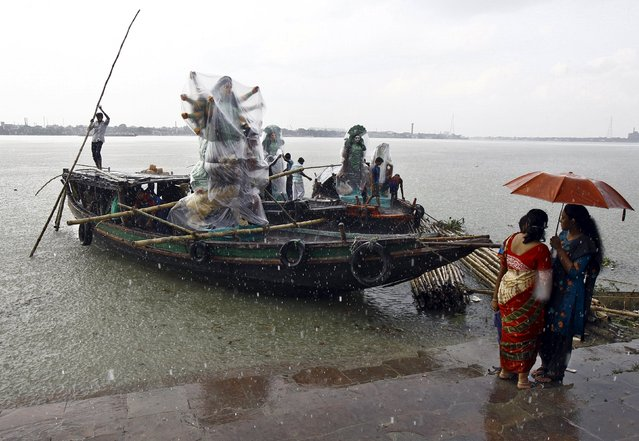 Devotees stand under an umbrella as the idols of Hindu goddess Durga are being transported on boats through the waters of river Ganga during a rain shower ahead of the Durga Puja festival in Kolkata, India, October 15, 2015. (Photo by Rupak De Chowdhuri/Reuters)