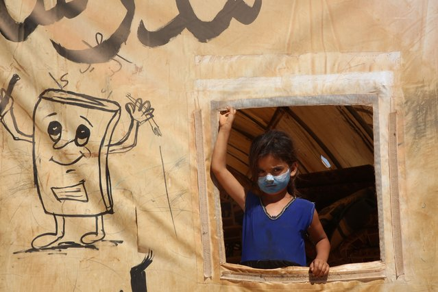 The young artist, Osama Alali, 13, draws masks on the faces of children in the Al-Anwar IDP camp, west of the city of Maarat Misrin, northwest of Idlib Governorate, Syria on September 16, 2020 to spread awareness in the camp about prevention methods. The spread of the new Corona virus.(Photo by Muhammad al-Rifai/NurPhoto via Getty Images)