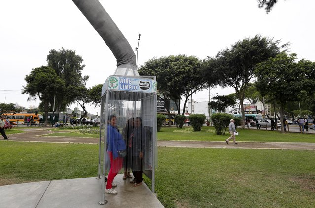 "People breathe fresh air from a giant air purifier, which its inventor calls a ""super tree"", in Lima's district of Jesus Maria November 24, 2014. (Photo by Mariana Bazo/Reuters)"