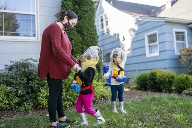 Jessica Walker (L-R) plays with her twin daughters Eleanor Walker and Buddy Mae Walker, 4, while trying on child respirators provided by the non-profit TeamRaccoonPDX on October 6, 2020 in Portland, Oregon. We told them their grandparents sent them space suits to keep them safe, Jessica Walker said of the respirators, which the family sought out after police used tear gas near their residential street. (Photo by Nathan Howard/Getty Images)