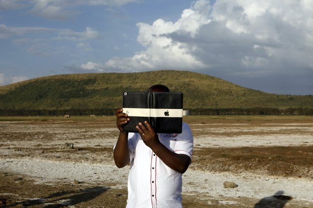 A tourist takes pictures at Lake Nakuru National Park, Kenya, August 18, 2015. (Photo by Joe Penney/Reuters)