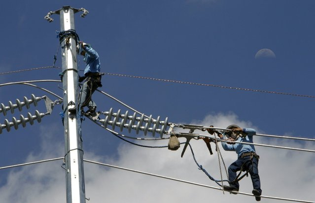 Workers balance on a cable while installing an electric line at a busy street in Manila March 19, 2013. Manila Electric Company (MERALCO), the Philippines biggest power utility, said earlier this month its customers could expect a marginal increase in their electricity bills for March due to the imposition of a new universal charge for stranded contract costs by a state-run energy agency. Electricity in the Philippines is one of the most expensive in Asia, hurting the pockets of consumers and businesses. (Photo by Romeo Ranoco/Reuters)