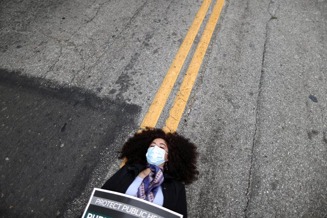 A woman lies in the road outside the LA Board of Supervisors during a die-in protest and memorial service honoring the over 6,800 people from LA who died from the coronavirus disease (COVID-19), in Los Angeles, California, U.S., October 21, 2020. (Photo by Lucy Nicholson/Reuters)