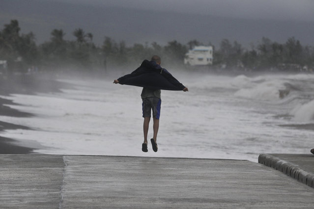 A resident jumps as he watches strong waves crash into shore as an effect of Typhoon Hagupit in Legazpi, Albay province, eastern Philippines on Sunday, December 7, 2014. Typhoon Hagupit knocked out power in entire coastal provinces, mowed down trees and sent more than 650,000 people into shelters before it weakened Sunday, sparing the central Philippines a repetition of unprecedented devastation by last year's storm. (Photo by Aaron Favila/AP Photo)