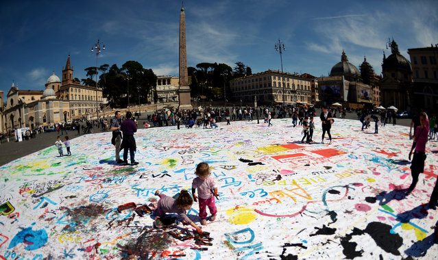 """Children paint on a giant canvas in Rome's central Piazza del Popolo on April 7, 2013 during a performance named """"What's good for families is good for the country"""" organised by the city's cultural association """"Kitchen Art"""" aiming to make the Italian captial a family-friendly city. (Photo by Gabriel Bouys/AFP Photo)"""