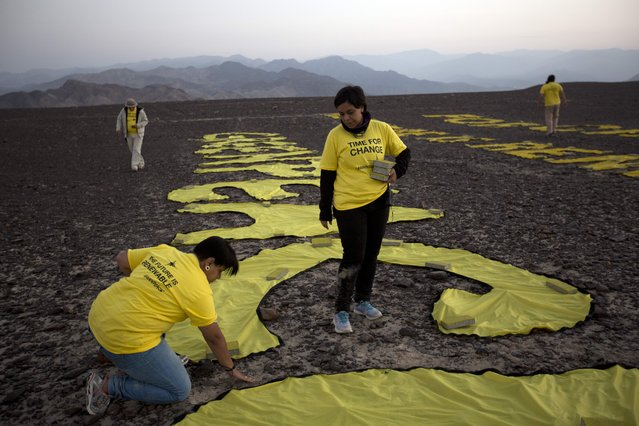 "Greenpeace activists arrange the letters delivering the message ""Time for Change: The Future is Renewable"" next to the hummingbird geoglyph in Nazca, Peru, Monday, December 8, 2014. (Photo by Rodrigo Abd/AP Photo)"
