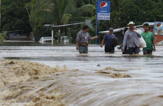 Men wade through a street flooded after the passing of Hurricane Iota in La Lima, Honduras, Wednesday, November 18, 2020. Iota flooded stretches of Honduras still underwater from Hurricane Eta, after it hit Nicaragua Monday evening as a Category 4 hurricane and weakened as it moved across Central America, dissipating over El Salvador early Wednesday. (Photo by Delmer Martinez/AP Photo)