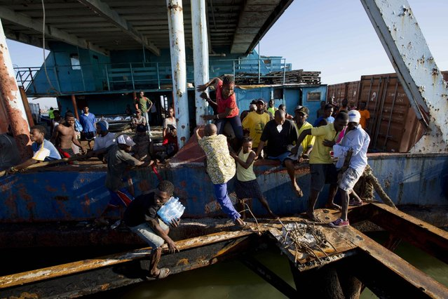 """People try to get off a boat carrying aid as national police arrive to secure the vessel carrying supplies as it docks in Jeremie, Haiti, Wednesday October 12, 2016, after Hurricane Matthew hit the area. The U.N. envoy for Haiti says the impoverished Caribbean nation is facing """"a humanitarian tragedy and an acute emergency situation"""" with 1.4 million people needing immediate help. (Photo by Dieu Nalio Chery/AP Photo)"""