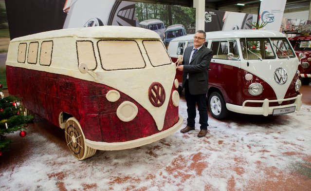 German car dealer Rudi Dietl, who had the idea for the gingerbread Volkswagen bus, stands between the Volkswagen T1 mini bus made of gingerbread (L) and the original car model in Hanover, Germany, 17 December 2014. The gingerbread bus weighs 450 kilograms. The construction is based on a wooden frame and hot chocolate was used as a glue to attach gingerbread to the frame of the bus. (Photo by Julian Stratenschulte/EPA)