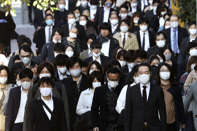 Commuters wearing face masks to protect against the spread of the coronavirus walk on a street in Tokyo, Tuesday, November 17, 2020. (Photo by Koji Sasahara/AP Photo)
