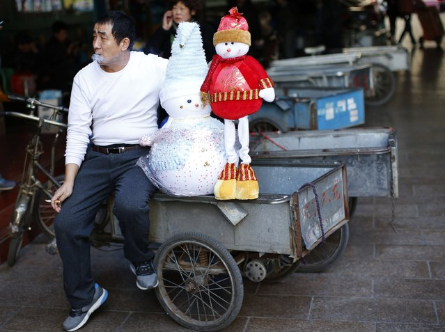 A vendor smokes a cigarette as he takes a break while he selling Christmas decorations at a shopping mall in Beijing December 24, 2014. Christmas is not a traditional festival in China but is growing in popularity, especially in more metropolitan areas where young people go out to celebrate, give gifts and decorate their homes. (Photo by Kim Kyung-Hoon/Reuters)