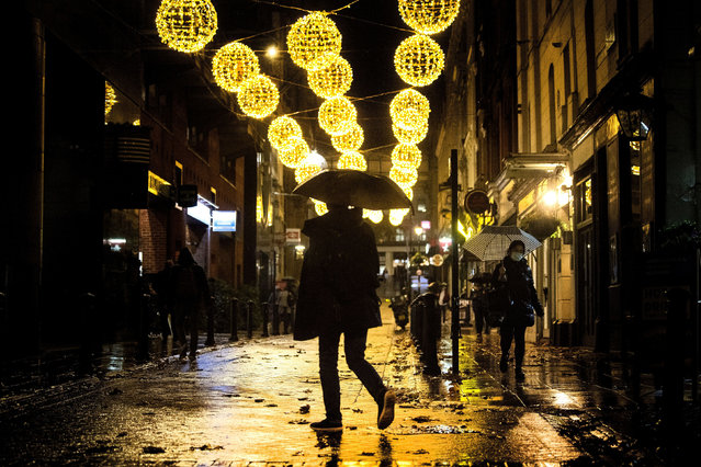 A man crosses a quiet street filled with Christmas lights in central London, Monday November 9, 2020. Wet weather has drenched the London streets during the first full week of a four-week coronavirus lockdown in England, as some are calling to allow businesses to open their doors to kickstart the city economy. (Photo by Victoria Jones/PA Wire via AP Photo)