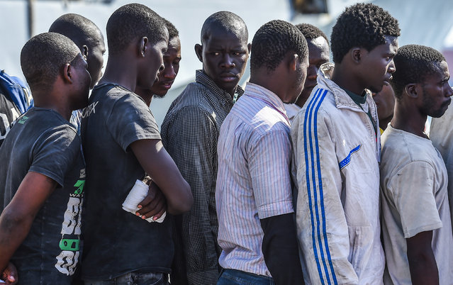 African migrant men wait in line to have medical evaluations after disembarking from the Italian Navy ship Foscari on August 23, 2014 in Portopalo di Capo Passero, Italy. The migrants were rescued in the Mediterranean Sea after leaving Libya for Italy on a raft. Thousands of migrants from Africa and the Middle East are coming ashore to Italy trying to escape conflict in their homelands. (Photo by Ricky Carioti/The Washington Post)