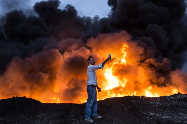 A man takes a selfie in front of a fire from oil that has been set ablaze in the Qayyarah area, some 60 kilometres (35 miles) south of Mosul, on October 19, 2016, during an operation by Iraqi forces against Islamic State (IS) group jihadists to retake the main hub city. In the biggest Iraqi military operation in years, forces have retaken dozens of villages, mostly south and east of Mosul, and are planning multiple assaults for October 20. (Photo by Yasin Akgul/AFP Photo)