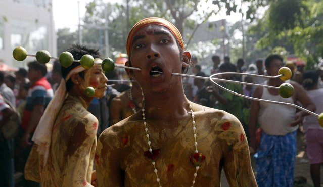 Myanmar Hindu devotees stands with his mouth pierced with a metal stick while waiting to walk on burning embers during a traditional Hindu fire festival in Yangon, Myanmar, Sunday, May 5, 2013. (Photo by Khin Maung Win/AP Photo)