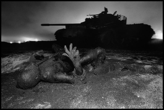 Kuwait, 1991. Next to a tank destroyed by US aerial bombing, a dead Iraqi soldier is mummified by drops of oil escaping from wells, set on fire by the soldier's unit before it retreated. (Photo by Abbas Attar/Magnum Photos)