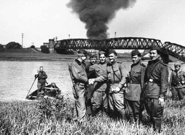 A group of Russian soldiers who met the Americans on the other side of the Elbe, Germany, on April 27, 1945. A burning building can be seen in the background. (Photo by AP Photo)