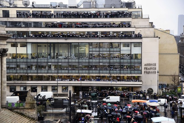 "Journalists of international press agency Agence France-Presse (AFP) hold signs reading ""Je suis Charlie"" (I am Charlie) at their headquarters in Paris as they observe a minute of silence on January 8, 2015 for the victims of an attack by armed gunmen on the offices of French satirical newspaper Charlie Hebdo in Paris on January 7 which left at least 12 dead and many others injured. (Photo by Francois Xavier Marit/AFP Photo)"
