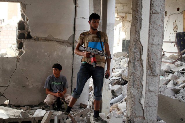 Fighters of Libyan forces allied with the U.N.-backed government take cover in a ruined house near the front line of fighting with Islamic State militants in Ghiza Bahriya district, in Sirte, Libya October 28, 2016. (Photo by Hani Amara/Reuters)