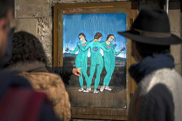 """People look at a painting by Italian street artist TvBoy named """"The three Vaccines"""" depicting The Three Graces by Italian painter Raphael in Barcelona, Spain, Friday, January 22, 2021. Although health authorities believe that the surge of coronavirus infections is waning, the rate of contagion has shot to over three times the extreme risk level, dangerously straining the health system. (Photo by Emilio Morenatti/AP Photo)"""