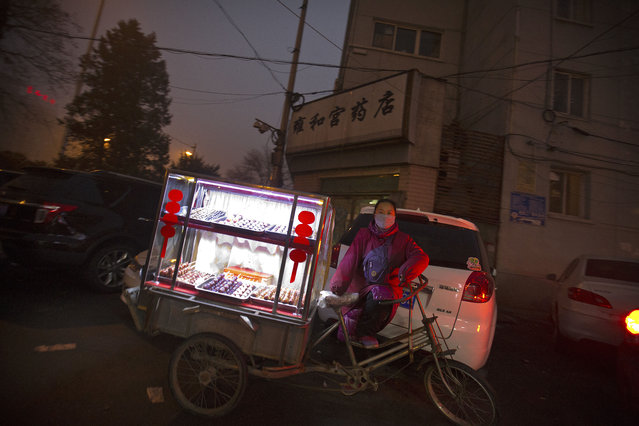 A woman selling snacks waits with her bicycle cart outside of a subway station amid heavy pollution and fog in Beijing, Tuesday, December 1, 2015. Schools in the Chinese capital kept students indoors and parents brought their kids to hospitals with breathing ailments today as Beijing grapples with extremely severe air pollution for the fifth straight day. (Photo by Mark Schiefelbein/AP Photo)