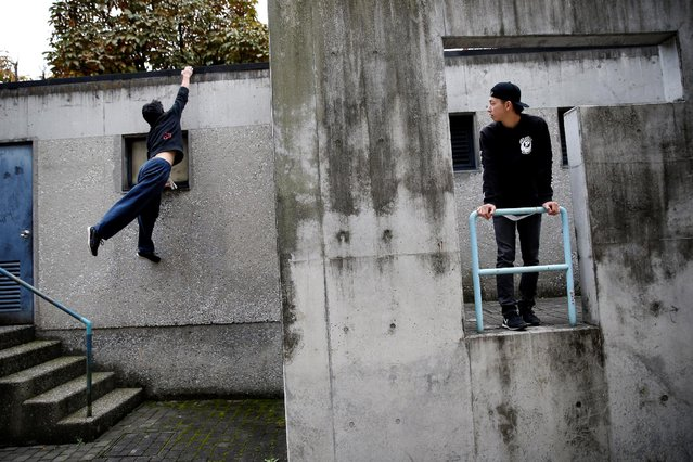 A parkour practitioner looks at Jun Sato, founder of Japan's first parkour educational institute SENDAI X-TRAIN, while Jun demonstrates his parkour skill at a park in Tokyo, Japan November 2, 2016. (Photo by Kim Kyung-Hoon/Reuters)