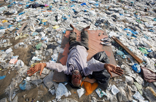 A man exercises on a garbage-strewn beach on World Environment Day in Mumbai, India, June 5, 2018. (Photo by Francis Mascarenhas/Reuters)