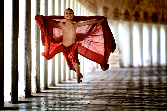 """""""Flying Monk"""". Young monks begin their service very early in life in their studies in the monastery. This monk was young and energetic and decided to """"fly"""" in his exuberance for life. Location: Mandalay, Myanmar. (Photo and caption by Bonnie Stewart/National Geographic Traveler Photo Contest)"""