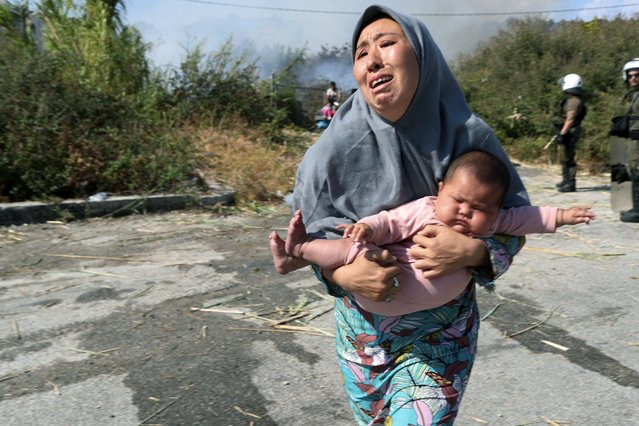 A migrant holds her baby as she runs to avoid a small fire in a field near Mytilene town, on the northeastern island of Lesbos, Greece, Saturday, September 12, 2020. Thousands of asylum-seekers spent a fourth night sleeping in the open on the Greek island of Lesbos, after successive fires destroyed the notoriously overcrowded Moria camp during a coronavirus lockdown. (Photo by Petros Giannakouris/AP Photo)