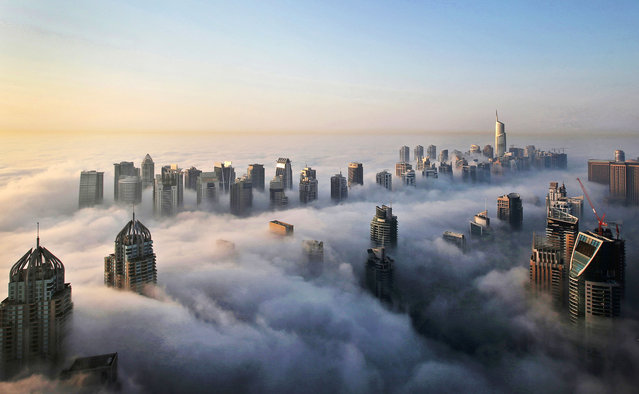 In this Monday, October 5, 2015 photo, a thick blanket of early morning fog partially shrouds the skyscrapers of the Marina and Jumeirah Lake Towers districts of Dubai, United Arab Emirates. Dubai's rapid transformation from a desert outpost into one of the world's most architecturally stunning cities is mapped out in the Marina. Where just 15 years ago there was empty, flat land, today a bustling neighborhood thrives centered around a canal and an impressive skyline that pierces through the clouds. (Photo by Kamran Jebreili/AP Photo)
