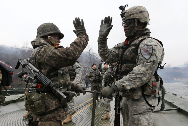 Soldiers from South Korea (L) and the US (R) gesture as they set up a floating bridge during a US-South Korea joint river crossing exercise in the border county of Yeoncheon, northeast of Seoul, on December 10, 2015. The Korean peninsula is the world's last Cold War frontier as Stalinst North Korea and pro-Western South Korea have been technically at war since the 1950-53 Korean War. (Photo by AFP Photo/Yonhap)