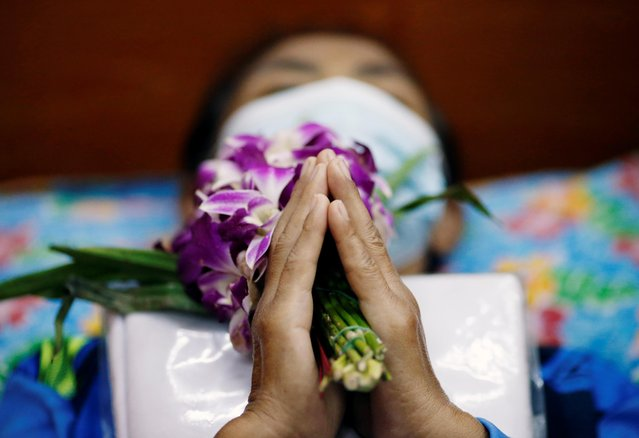 A devotee lies down and prays inside a coffin to trick death and improve luck at a temple in Bangkok, Thailand on January 27, 2021. (Photo by Soe Zeya Tun/Reuters)