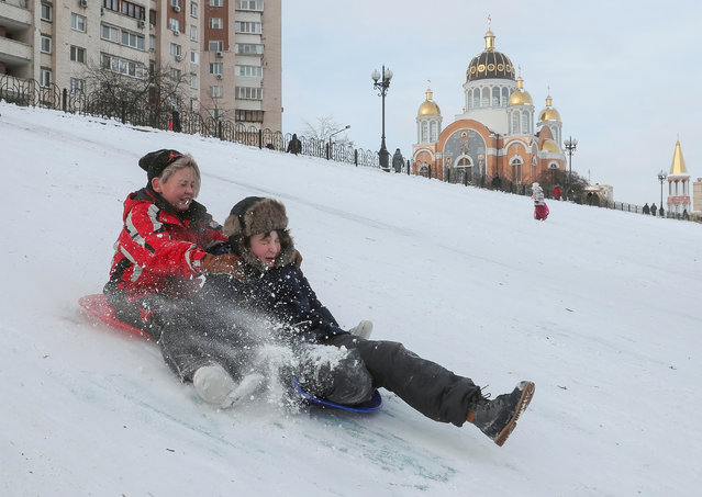 Ukrainian children fool around on a snow-covered hill in Kiev, Ukraine, 18 January 2021. A strong frost with temperatures up to minus 20 degrees Celsius has continued in Ukraine for several last days. (Photo by Sergey Dolzhenko/EPA/EFE)