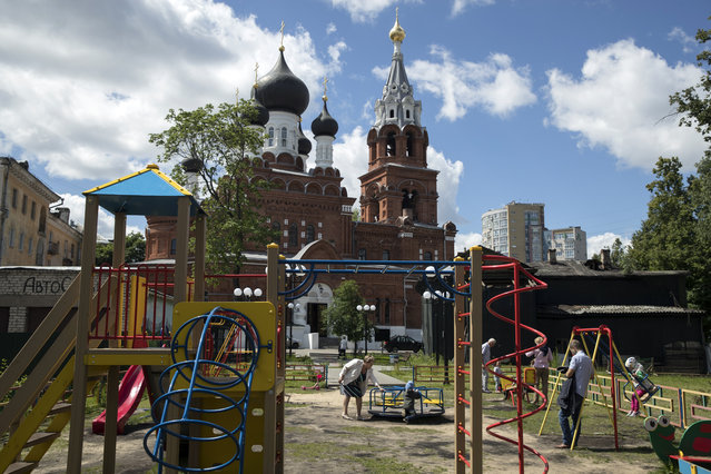 In this Wednesday, June 20, 2018 filer, People play with children in front of the Orthodox church in Nizhny Novgorod, Russia. (Photo by Pavel Golovkin/AP Photo)