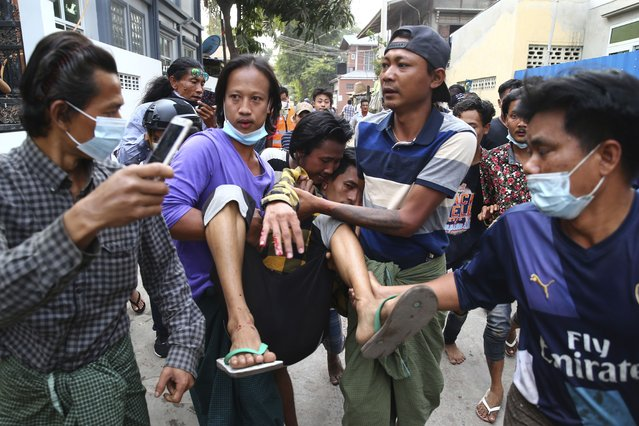 A man is carried after police dispersed protesters in Mandalay, Myanmar on Saturday, February 20, 2021. Security forces in Myanmar ratcheted up their pressure against anti-coup protesters Saturday, using water cannons, tear gas, slingshots and rubber bullets against demonstrators and striking dock workers in Mandalay, the nation's second-largest city. (Photo by AP Photo/Stringer)