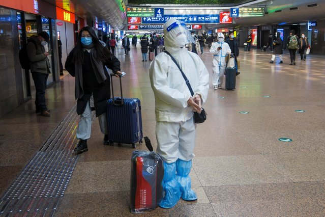 People wearing protective suits walk in the Beijing West railway station ahead of upcoming Chinese New Year celebrations following an outbreak of the coronavirus disease (COVID-19) in Beijing, China, January 27, 2021. (Photo by Thomas Peter/Reuters)