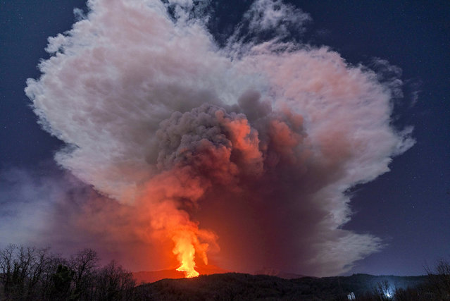 A fiery river of glowing lava flows on the north-east side of the Mt Etna volcano engulfed with ashes and smoke near Milo, Sicily, Wednesday night, February 24, 2021. (Photo by Salvatore Allegra/AP Photo)
