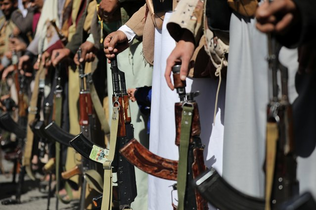 Houthi supporters hold their weapons during a demonstration outside the U.S. embassy against the United States over its decision to designate the Houthis a foreign terrorist organisation, in Sanaa, Yemen on January 18, 2021. (Photo by Khaled Abdullah/Reuters)