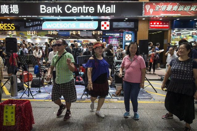 People dance to buskers performances in Sai Yeung Choi Street South in Mongkok district, Hong Kong, China, 28 July 2018. (Photo by Jerome Favre/EPA/EFE)
