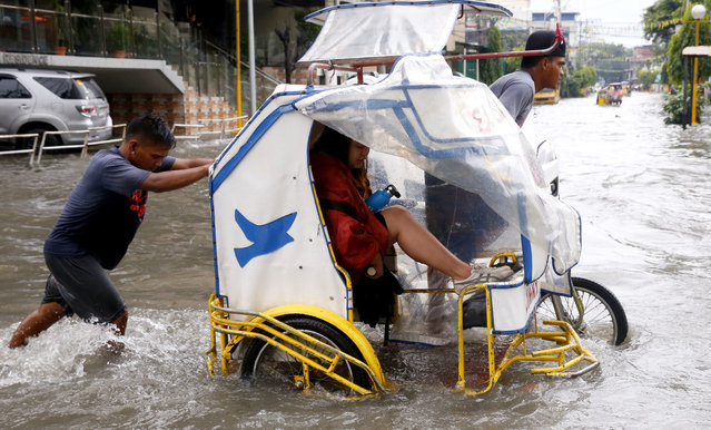 A commuter raises her feet to stay dry as she rides a pedicab, a pedaled tricycle, to go to work amidst flooding after overnight Southwest monsoon rains brought about by tropical storm Ampil inundated low-lying areas in Metropolitan Manila and nearby provinces Friday, July 20, 2018 in Manila, Philippines. (Photo by Bullit Marquez/AP Photo)