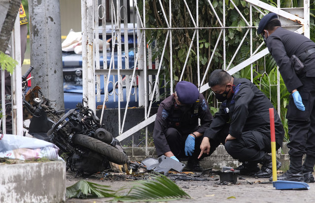 Members of a police bomb squad inspect the wreckage of a motorbike used to carry out Sunday's suicide bomb attack at the Sacred Heart of Jesus Cathedral in Makassar, South Sulawesi, Indonesia, Monday, March 29, 2021. Two attackers believed to be members of a militant network that pledged allegiance to the Islamic State group blew themselves up outside the packed Roman Catholic cathedral during a Palm Sunday Mass on Indonesia's Sulawesi island, wounding a number of people, police said. (Photo by Masyudi S. Firmansyah/AP Photo)