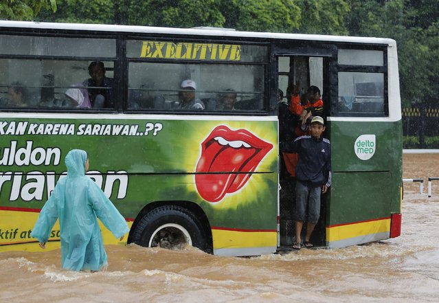 A bus drives through flood waters outside the Presidential Palace, after heavy seasonal rains flooded parts of Jakarta February 9, 2015. (Photo by Darren Whiteside/Reuters)