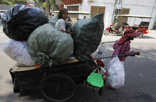 A woman pulls a cart as her daughter sits on sacks of cans after they collected the cans from the streets behind the Royal Palace in Phnom Penh February 9, 2015. (Photo by Samrang Pring/Reuters)