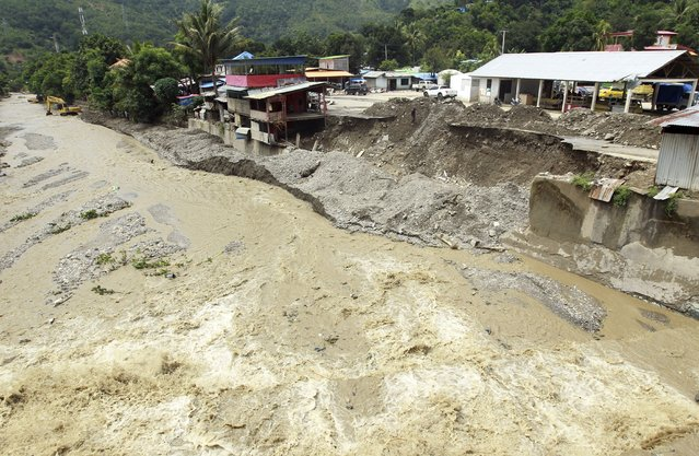 A collapsed retaining wall sits along the banks of a flooded river in Dili, East Timor, Tuesday, April 6, 2021. Several disasters brought on by severe weather in eastern Indonesia and neighboring East Timor have left a number of people dead or missing. (Photo by Kandhi Barnez/AP Photo)