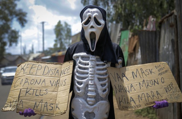 James Kiriva, 35, who took the initiative to educate his community about the importance of taking precautions to curb the spread of the coronavirus and COVID-19, walks around dressed as a skeleton to spread his message in English and Swahili in the Kibera low-income neighborhood of Nairobi, Kenya Tuesday, April 13, 2021. (Photo by Brian Inganga/AP Photo)