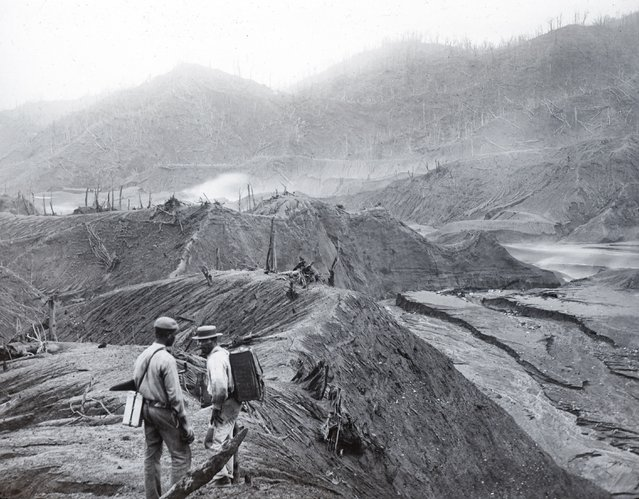 In this 1902 photo provided by York Museums Trust, men survey the devastation of the landscape following eruptions of La Soufrière, a volcano on the island of St. Vincent in the Caribbean. On April 9, 2021, La Soufriere once again started spewing hot torrents of gas, ash and rock, forcing thousands to evacuate to government-run shelters and private homes. (Photo by Tempest Anderson/York Museums Trust via AP Photo)