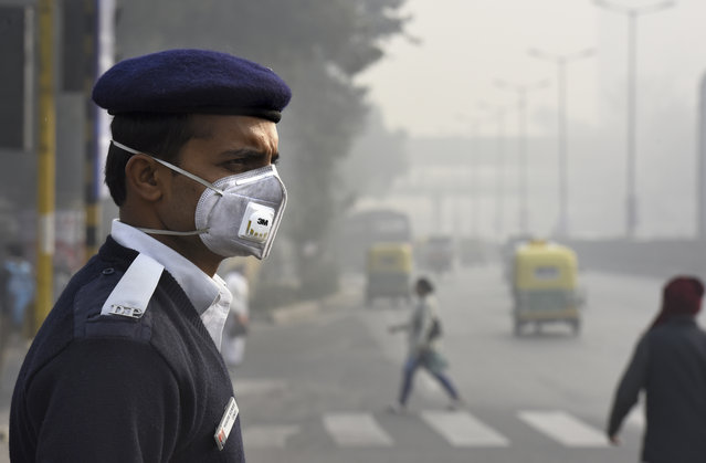 People and Traffic police wearing a mask during implementation Odd-Even Vehicle formula at ITO crossing on January 4, 2016 in New Delhi, India. Contrary to apprehensions, Delhi's odd-even vehicle scheme aimed at battling pollution did not lead to the feared problems on Monday, the first full working day of the new year. The 15-day odd-even scheme started on January 1 and aims to put odd numbered vehicles on the roads on odd dates and even numbered vehicles on even dates. (Photo by Arvind Yadav/Hindustan Times via Getty Images)